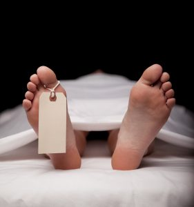 Deceased person covered in a sheet with a blank toe tag.