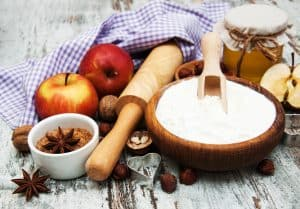 ingredients for apple pie - red apple, butter, flour, brown sugar, nuts and spices