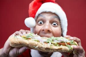 Excited young Santa man biting enormous sandwich on red background