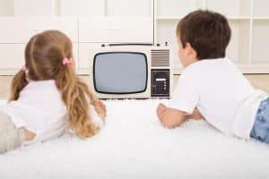Kids watching old television set laying on the floor